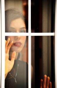 woman looking longingly through window